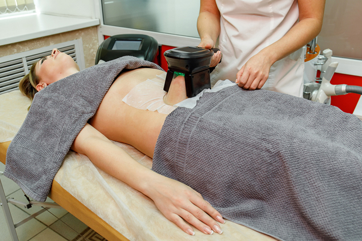 Female patient going through a body-sculpting treatment